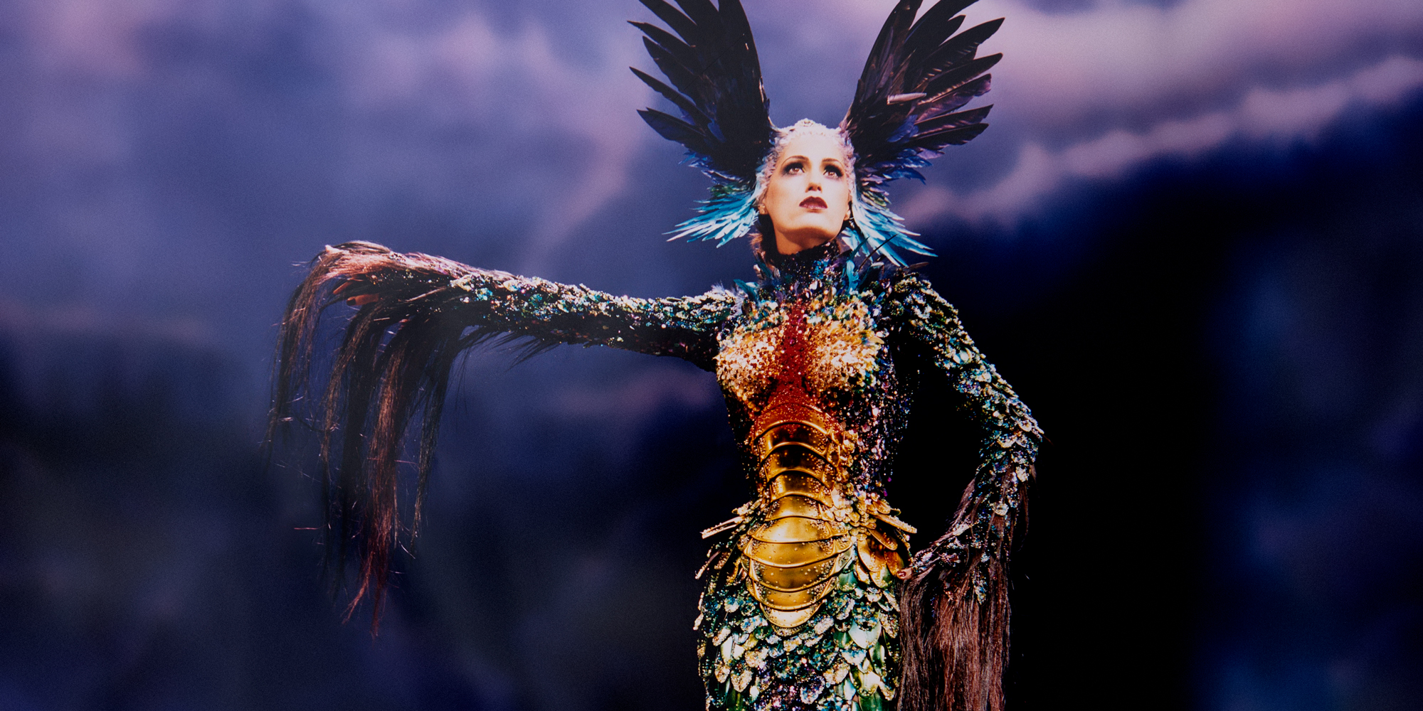 Alan Strutt, Yasmin Le Bon On Stage at the London Palladium, London, 1997; Evening Standard, October 31, 1997. Ensemble: Thierry Mugler, Chimera collection, haute couture fall/winter 1997-1998. Long sheath gown with scale-look body, feathers and horsehair embroidered with rhinestones, articulated golden bodice created in collaboration with Jean‑Jacques Urcun and Mr. Pearl.